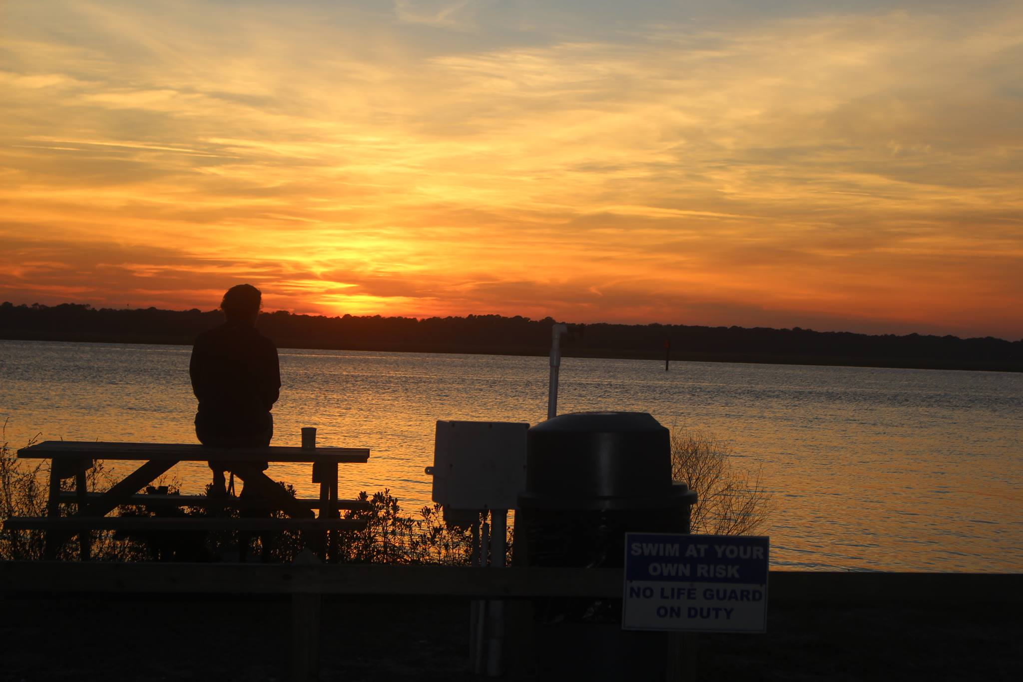 man standing on dock with sun in the background