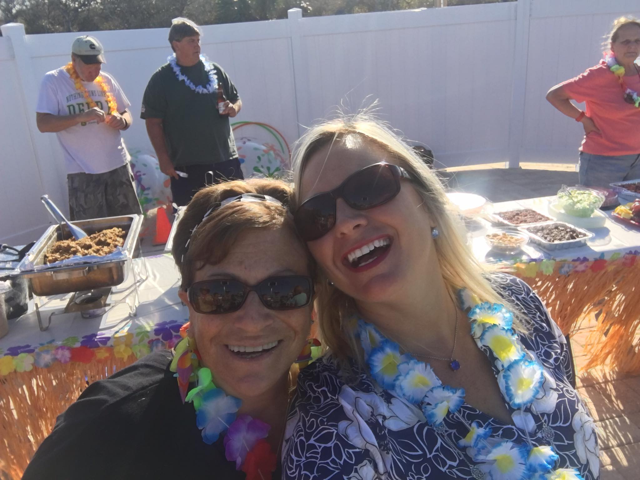 two women smiling wearing leis