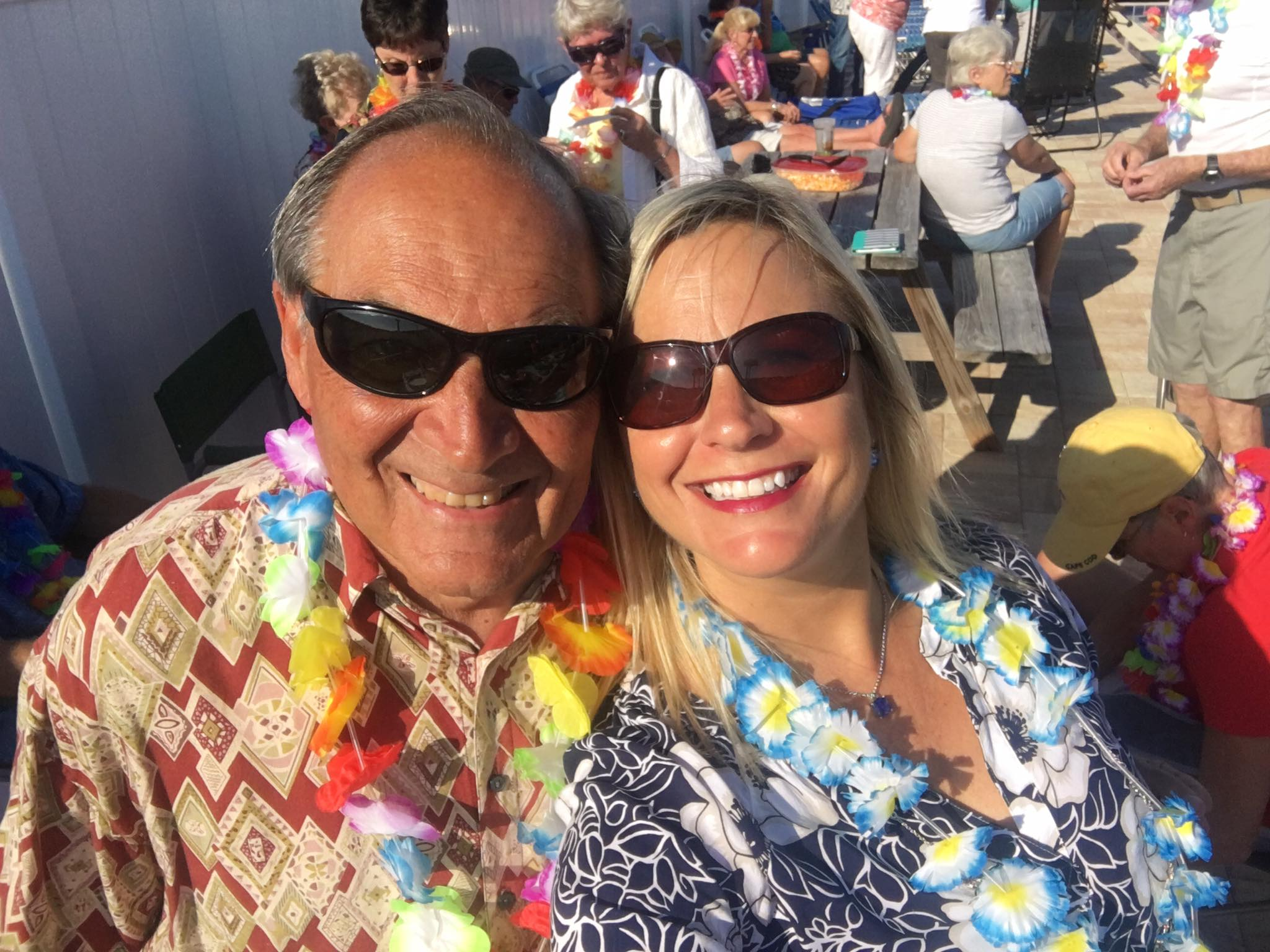 man and woman smiling wearing leis