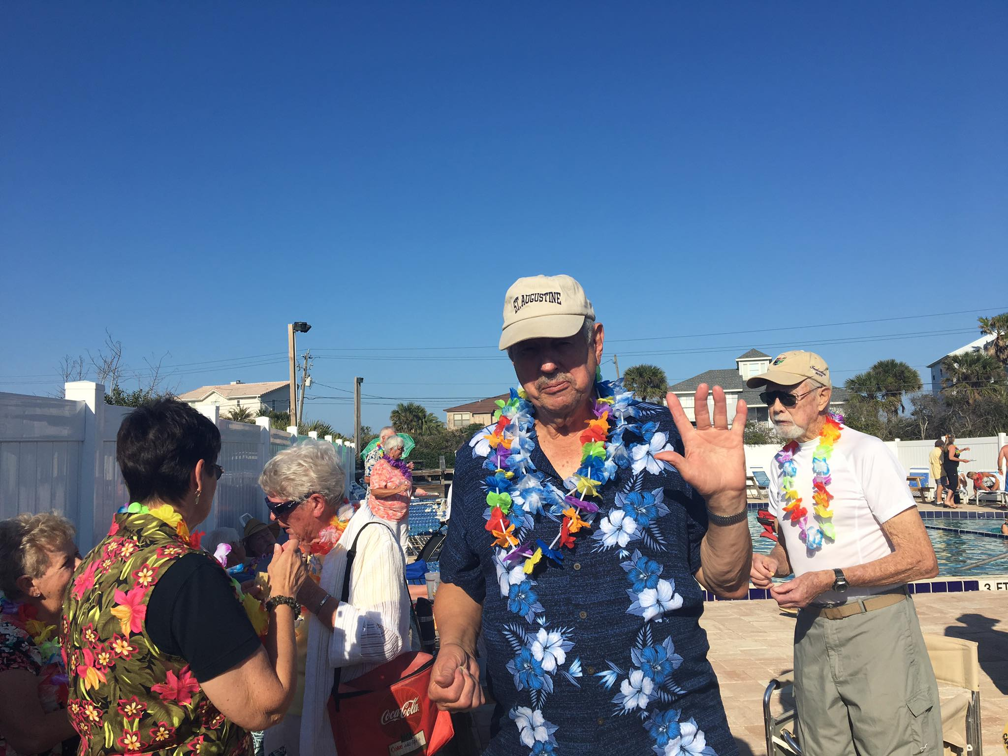 man wearing lei surrounded by other people