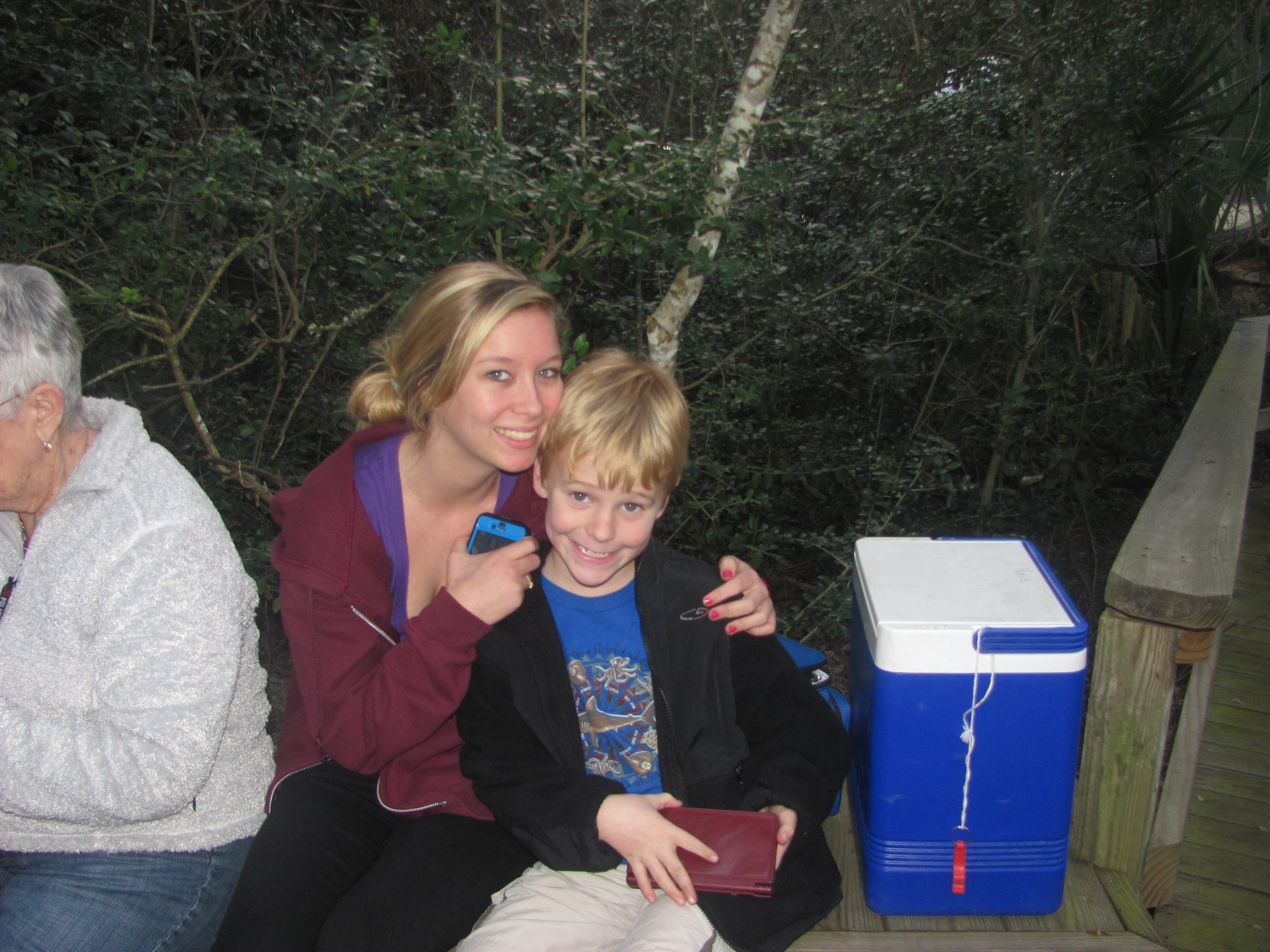 woman with young boy sitting next to blue cooler