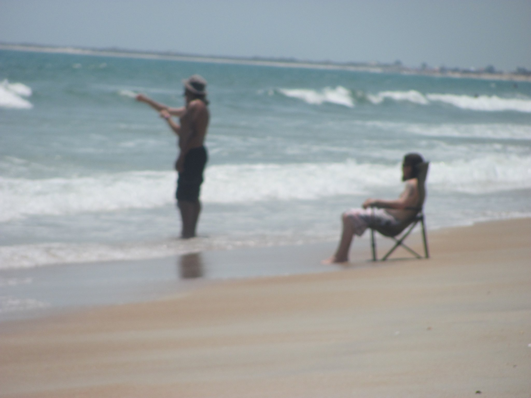 person fishing and another sitting in folding chair