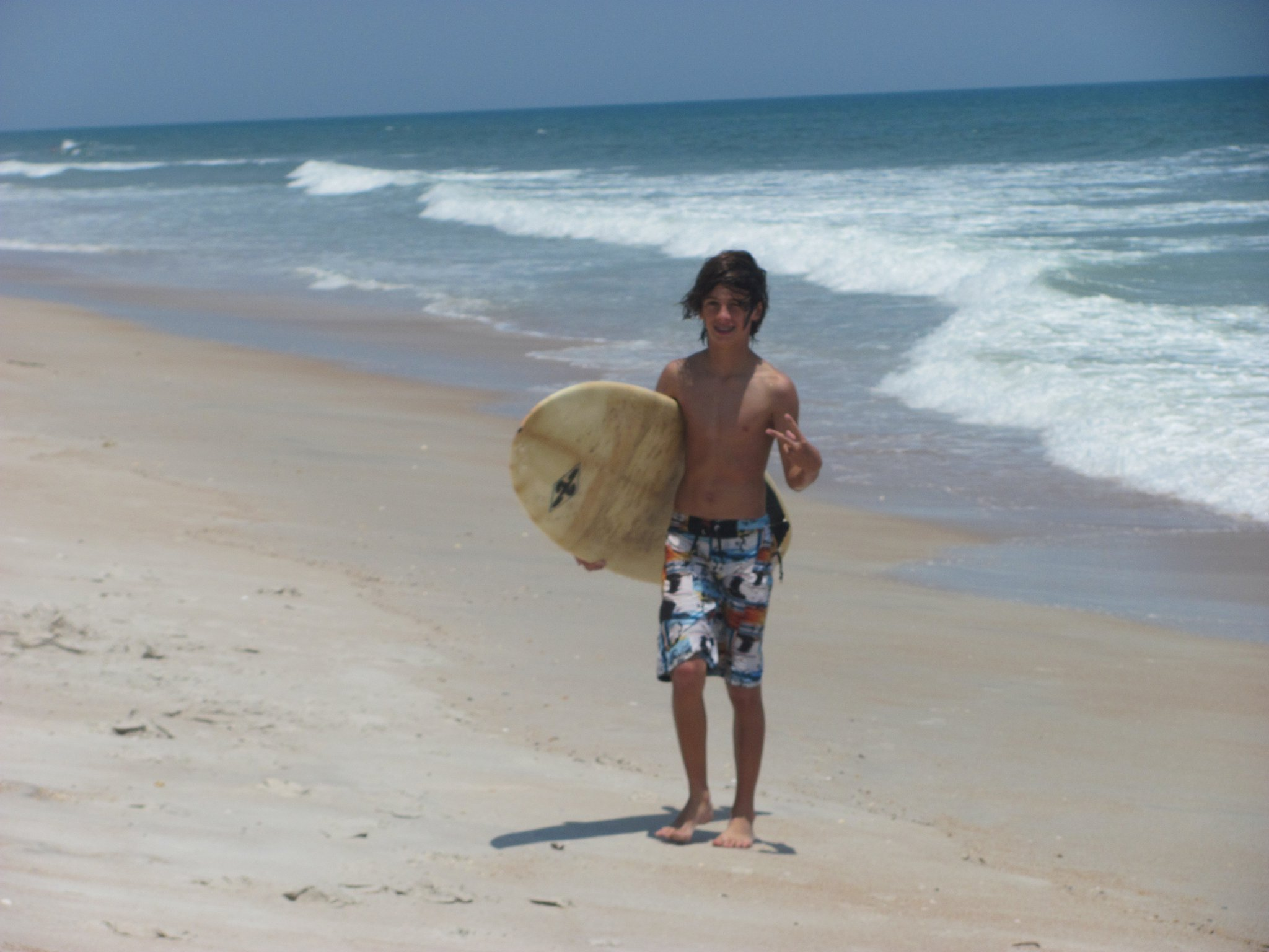 boy walking on beach with surfboard