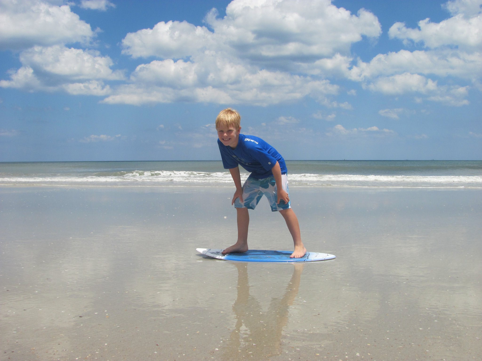 young boy standing on surfboard