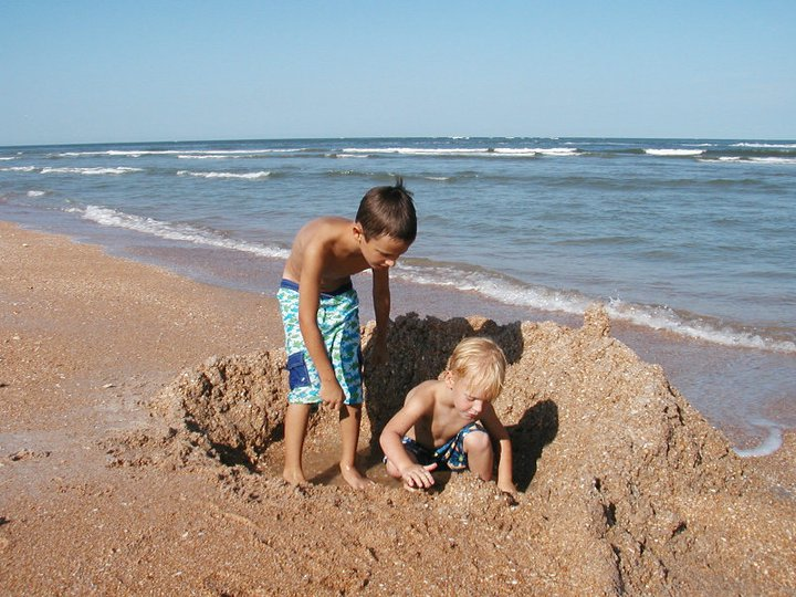 two young boys building a sandcastle