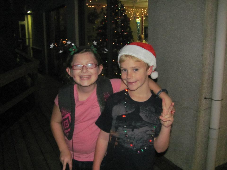 two young children one with christmas hat