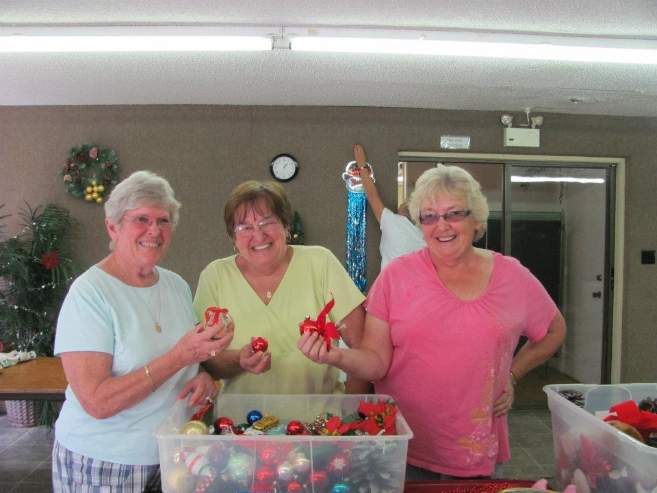 three women standing over decorations