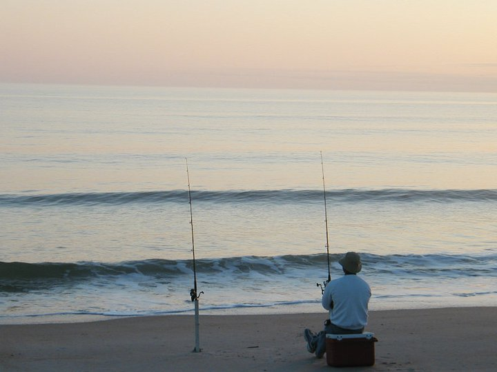 person fishing with extra fishing pole at ocean